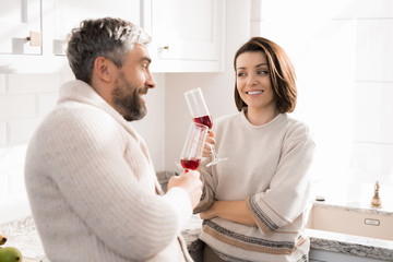 Warm toned waist up portrait of happy adult couple  drinking wine in kitchen  lit by sunlight
