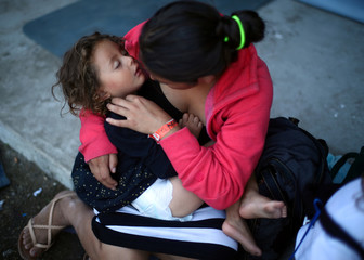Gizelle, a two-year-old migrant girl from Honduras, part of a caravan of thousands from Central America trying to reach the United States, sleeps in her mothers arms as they rest in a temporary shelter in Tijuana