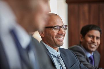 Smiling businessman with colleagues at meeting