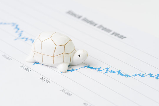 Sustainable with long term investment concept, miniature decorate turtle or tortoise slow walking on rising growth stock market value graph, value investment concept