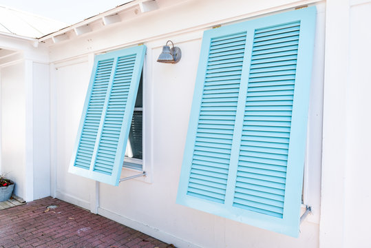 Pastel turquoise blue colorful hurricane window shutters closeup architecture open exterior of house in Florida beach home during sunny day, painted