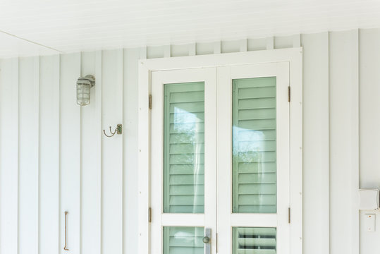 Pastel green colorful hurricane window shutters architecture open exterior of house in Florida beach home apartment building during day entrance, glass, lamp