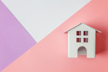Simply design with miniature white toy house isolated on white violet pink pastel colorful trendy geometric background. Mortgage property insurance dream home concept. Flat lay top view copy space
