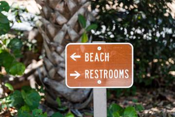 Beach Restrooms bathroom sign on street road in brown color in park on Sanibel Island, Florida