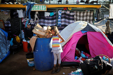 A migrant girl stands next to a tent at a temporary shelter in Tijuana