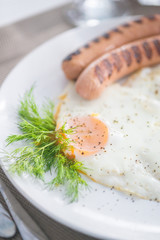 Traditional breakfast with  sausages, fried eggs, bread and yogurt