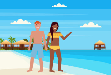 mix race couple on tropical island with villa bungalow hotel on beach seaside green palms landscape summer vacation concept flat horizontal