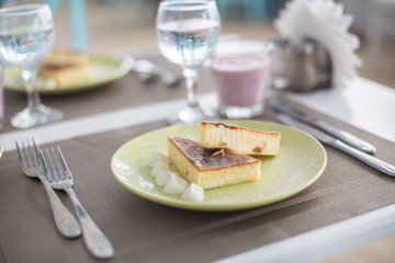 Cheese cake with   yogurt, whipped cream on a green plate. Tasty dessert decorated