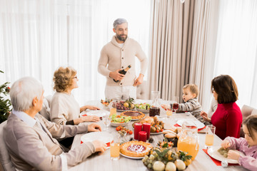 Warm-toned portrait of big happy family enjoying festive dinner together with mature father hosting table, copy space