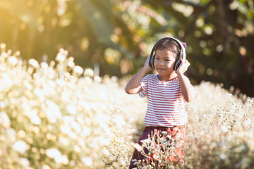 Cute asian child girl having fun to listen the music in headphones in flower field with happiness