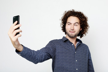 Portrait of a cheerful  man taking selfie over white background