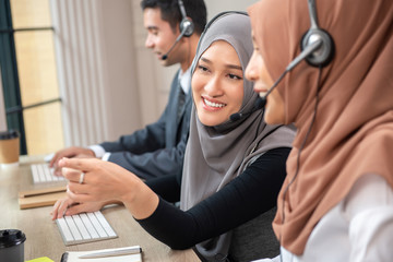Happy beautiful Asian muslim women working in call center office