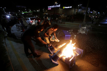 Demonstrators burn traffic cones at a barricade during a protest to mark the first anniversary of a contested presidential election with allegations of electoral fraud, in Tegucigalpa