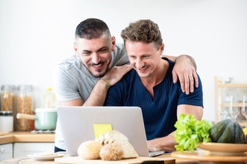 Happy gay male couple browsing internet together at home