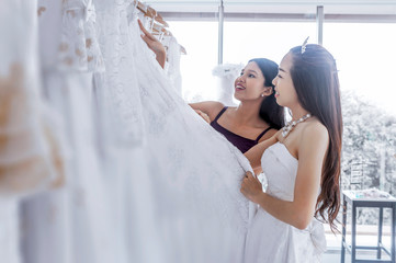 Bridesmaid helped to choose of brides lacy white and beautiful wedding dress.