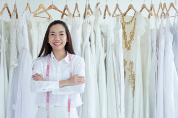Asian female smilling of bridal store owner standing with her arms crossed and smiling.