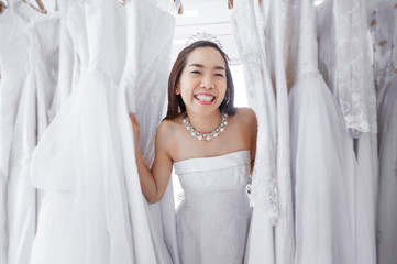 Beautiful female having fun during bridal gown fitting in wedding fashion store.
