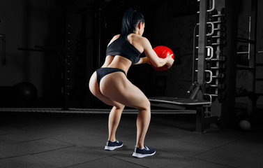 The girl crouches in the gym with the ball in her hands.