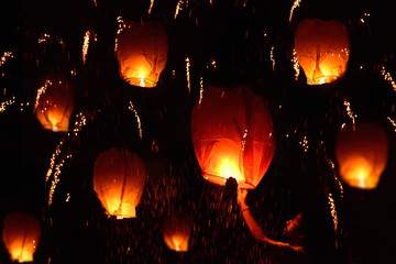 Man holding flying fire lantern to celebrate festival in a night sky.