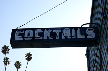 aged and worn vintage neon cocktail sign with palm trees