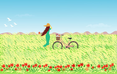 Woman in blue skirt wearing a hat with a bicycle standing in a field with reed flowers, the sky and mountains as the background.