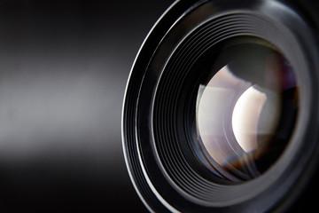 Camera lens on dark background close-up.