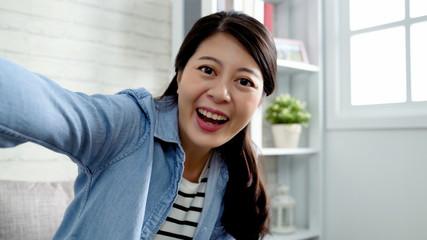 girl taking self portrait in cozy apartment