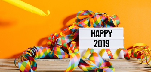 Happy 2019 greeting text in light box on party decorated backdrop