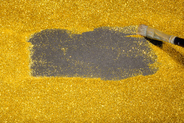 Paint brush revealing copy space on gold glitter luxury background