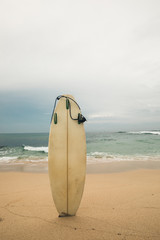 White Surfboard on sandy beach