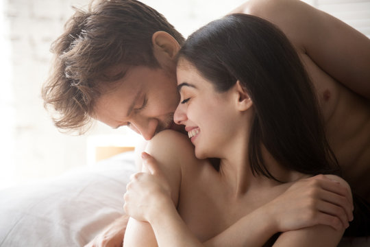 Passionate boyfriend kiss pretty smiling girlfriend shoulder during tender foreplay before love making in bedroom, young couple caressing, enjoying prelude before sex, romantic moment at home close up