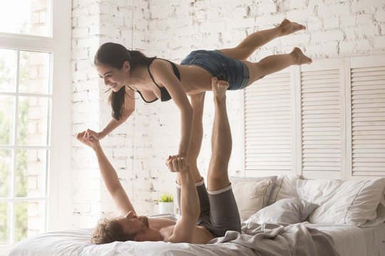 Loving young couple having acro yoga practice in bed at home, sporty strong shirtless man holding slender attractive woman, happy smiling girlfriend doing sport exercise with boyfriend, trust concept