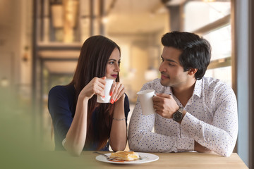 Happy young couple having hot drink at restaurant table