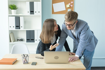 Business, teamwork and people concept - Portrait of serious man and attractive woman working at project in office.