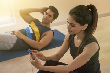 Young couple doing exercise on floor using mobile phone