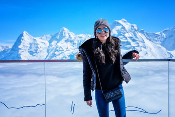 Young Woman Tourist at Schilthorn in Switzerland with a magnificent panoramic view of the Swiss Skyline.
