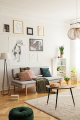 Posters above settee with pillows in bright living room interior with pouf next to table. Real photo