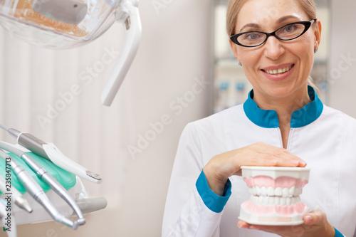 Mature female dentist smiling joyfully to the camera, holding