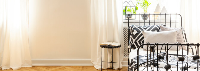 Patterned sheets on bed next to black table in white bedroom interior with copy space. Real photo