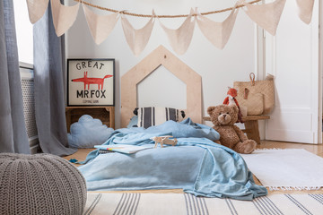 Blue sheets on bed and grey pouf in kid's bedroom interior with poster and plush toy. Real photo