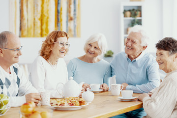 Group of happy older people laughing together on a coffee meeting at nursing home