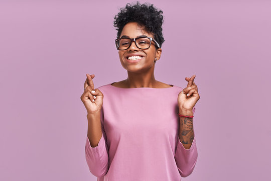 I have to win. Portrait of young female has dark skin, clenches teeth, raises fingers crossed, makes desirable wish, wears round spectacles and casual clothes, waits for good news