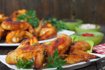 Roasted chicken wings with spices on wooden background