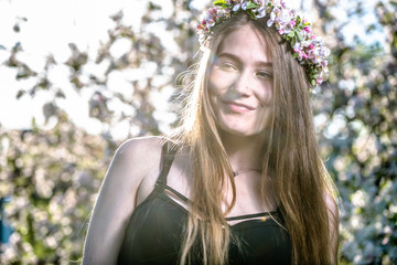 Beautiful smiling innocent pure girl in a wreath with flowers of white apple blossom, spring outdoor portrait of woman face with arms