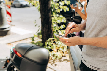 A guy or a tourist activates or rents an electric scooter using a mobile application on a cell phone to travel around the city. Electric scooter is a popular vehicle in Berlin in Germany.