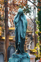Grieving statue in an old European Catholic cemetery at sunset.