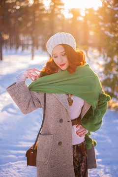 Young beautiful woman in hat walks in a snow-covered park among Christmas trees. Winter sun flare