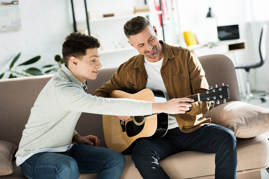 teen son teaching father play acoustic guitar at home
