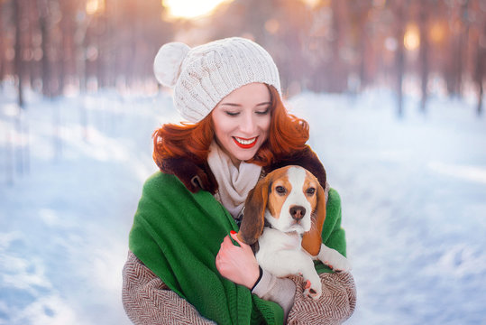 Young pretty woman with beagle dog at winter snow park. Makeup with bright red lips, wearing a green scarf.