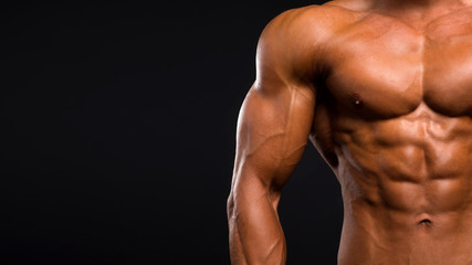 Low-key image of muscular masculine man over dark background